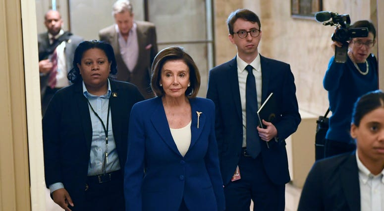 In this Friday, March 27, 2020 file photo, House Speaker Nancy Pelosi, D-Calif., arrives on Capitol Hill in Washington.