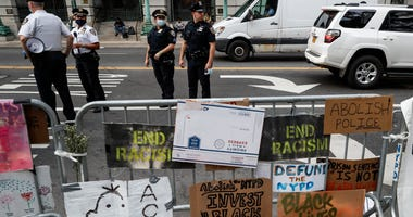 Police stand on the street beside a protest encampment surrounded by handmade signs and barricades outside City Hall, Friday, June 26, 2020, in New York.