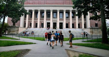In this Aug. 13, 2019 file photo, students walk near the Widener Library in Harvard Yard at Harvard University in Cambridge, Mass.