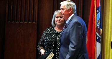 Gov. Mike Parson, right, smiles along side his wife, Teresa, after being sworn in as Missouri's 57th governor in Jefferson City, Mo.