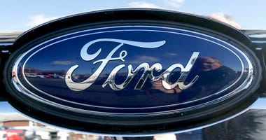 This Nov. 19, 2015 file photo shows the blue Ford oval badge in the grill of a pickup truck