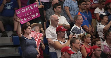 Guests listen as President Donald Trump speaks at a rally .