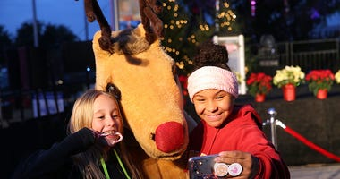 Guests take a selfie with Rudolph the Red-nosed Reindeer before the Texas Motor Speedway Tree Lighting and Grant Ceremony at Texas Motor Speedway on December 4, 2018 in Fort Worth, Texas.