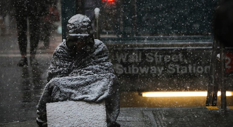 A homeless man sits in the falling snow in the Financial District, January 30, 2019 in New York City.
