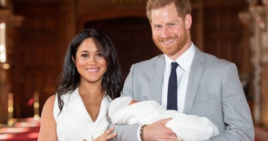 Prince Harry, Duke of Sussex and Meghan, Duchess of Sussex, pose with their newborn son during a photocall in St George's Hall at Windsor Castle on May 8, 2019 in Windsor, England.