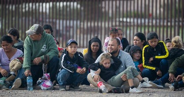 Migrants wait to be processed and loaded onto a bus by Border Patrol agents after being detained when they crossed illegally into the United States from Mexico