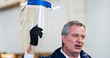 NEW YORK, NY - MARCH 26: New York Mayor Bill de Blasio holds a face shield as he speaks to the media during a visit to the Brooklyn Navy Yard where local industrial firms have begun manufacturing Personal Protective Equipment (PPE) on March 26, 2020