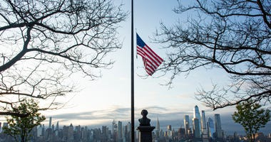 Flags are flying at half-mast as the sun rises behind in Manhattan on April 6, 2020 as seen from Weehawken, New Jersey.