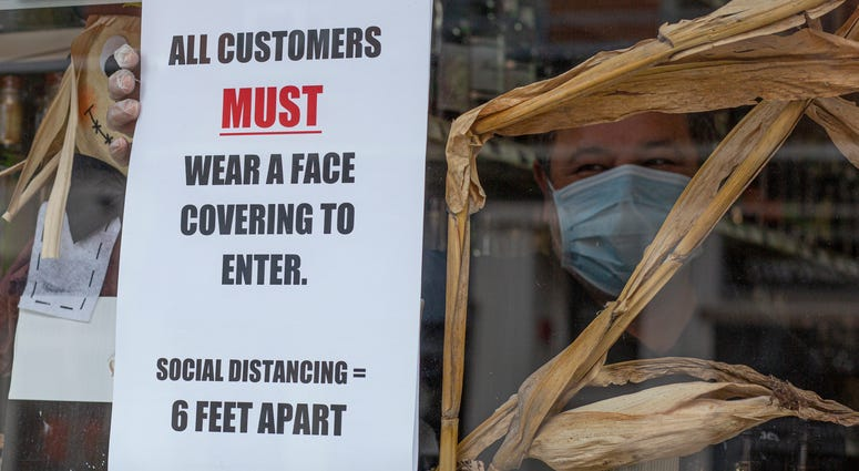 A worker places a placard on the window of a liquor store while wearing a face mask on April 10, 2020 in Jersey City, New Jersey.