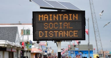 """A sign placed on the boardwalk states """"MAINTAIN SOCIAL DISTANCE"""" on May 24, 2020 in Wildwood, New Jersey."""