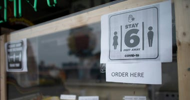 "A posted sign on a boardwalk restaurant states ""STAY 6 FEET AWAY"" on May 24, 2020 in Wildwood, New Jersey."