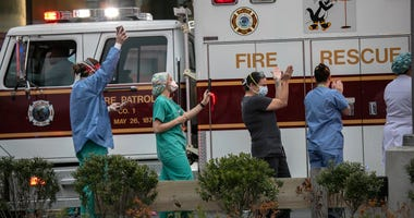 Hospital workers cheer as first responders pass by the Westchester Medical Center in a caravan of sirens and lights on April 14, 2020 in Valhalla, New York.
