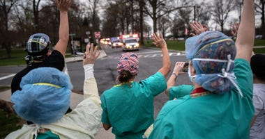 Hospital workers wave and cheer outside the Westchester Medical Center as first responders pass by in a caravan of sirens and lights on April 14, 2020 in Valhalla, New York.