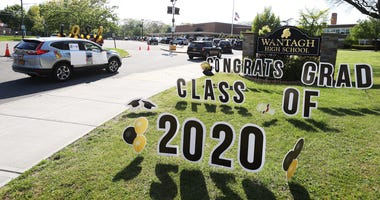 Graduating Seniors from Wantagh High School drive by the front of the school in a Class of 2020 Parade on May 15, 2020 in Wantagh, New York.