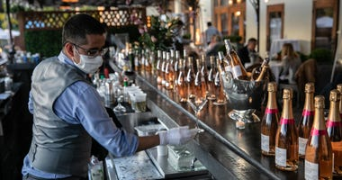 A bartender serves drinks at L'escale restaurant on May 20, 2020 in Greenwich, Connecticut.