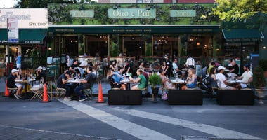People eat and drink at tables placed outside of a Manhattan restaurant as the city enters Phase 2 of re-opening following restrictions imposed to curb the coronavirus pandemic on June 24, 2020 in New York City.
