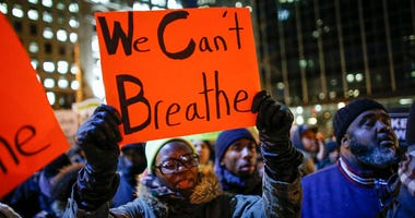 A woman holds a 'We Can't Breathe' sign at a protest following a grand jury's decision not to indict NYPD officers in the death of Eric Garner.