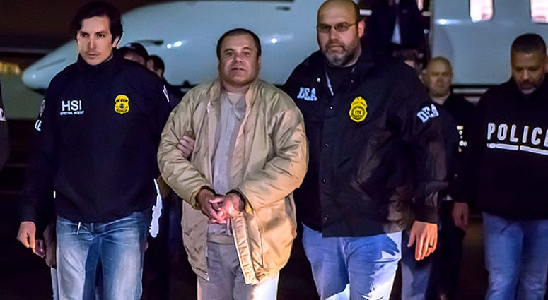 El Chapo is escorted by DEA agents.