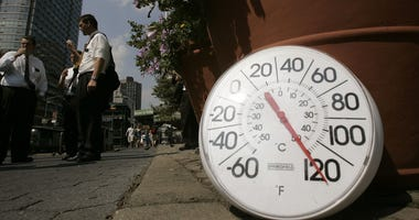 A thermometer in the sun on the sidewalk indicates a temperature of 120 degrees Fahrenheit as people eat ice cream on the Upper West Side August 2, 2006 in New York City.