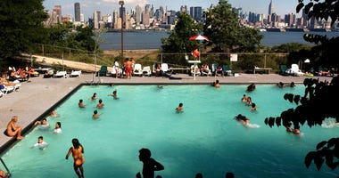 With the Manhattan skyline in the background, swimmers escape the heat July 10, 2002 in West New York, New Jersey.