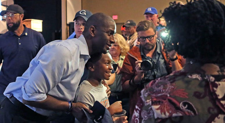 Tallahassee mMayor Andrew Gillum poses for a photo with a young fan during a campaign stop in his bid for governor, Monday, Nov. 5, 2018, in Crawfordville, Fla.