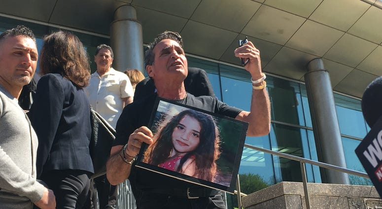 Karine Vetrano's father holds a picture of her outside of a sentencing hearing for her killer Chanel Lewis.