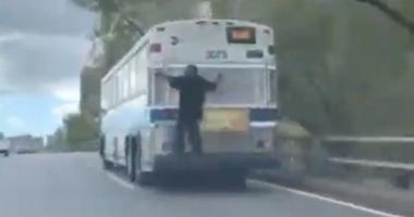 A man rides a bus down a New York City freeway