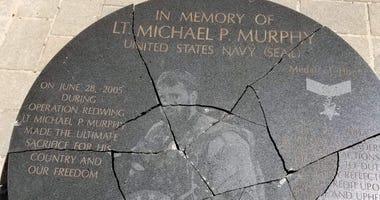 A teenager has been accused of vandalising a plaque dedicated to fallen Navy SEAL Lt. Michael Murphy.