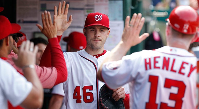 Patrick Corbin high-fives Washington Nationals teammates in the dugout.