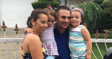 Pablo Villavicencio poses with his wife and 2 daughters outside their Hempstead home.