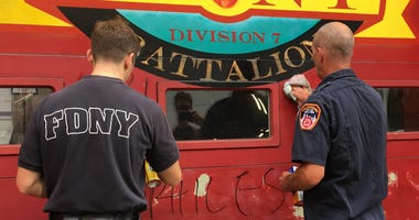 Firefighters in upper Manhattan scrub graffiti for the second time this week.