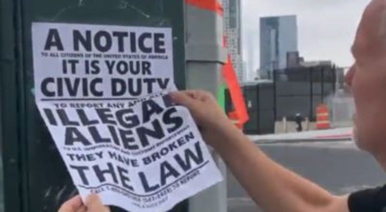 Councilman Jimmy Van Bramer tears down anti-immigrant fliers in Queens.