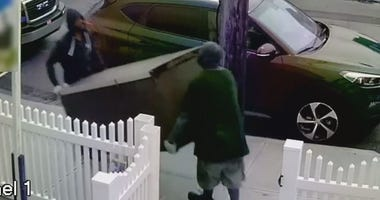 Two men walk out of a Queens apartment with a refrigerator during an alleged burglary.