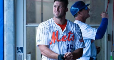 Tim Tebow takes off his batting gloves in the dugout of the Triple-A Syracuse Mets.