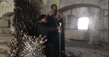 Game of Thrones fans sit on the Iron Throne in Brooklyn.