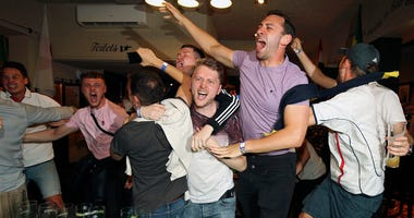 England supporters celebrate Harry Kane's winning goal as fans watch the World Cup soccer match between Tunisia and England at the Lord Raglan Pub in London, Monday, June 18, 2018.