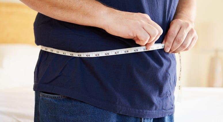 Close Up Of Overweight Man Measuring Waist