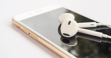Close-up image of earbuds on top of gold smartphone and reflection on screen isolate on white background