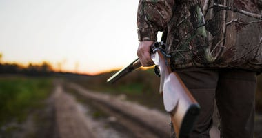 A hunter with a rifle walking on a dirt road.