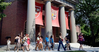 FILE - In this Aug. 30, 2012, file photo, a tour group walks through the campus of Harvard University in Cambridge, Mass.
