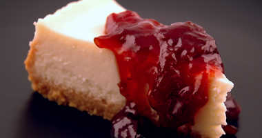 A slice of cheesecake topped with a cherry compote