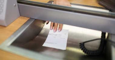 Clerk giving receipt at bank.