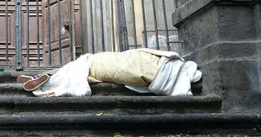 A homeless person sleeps on the steps of a church.