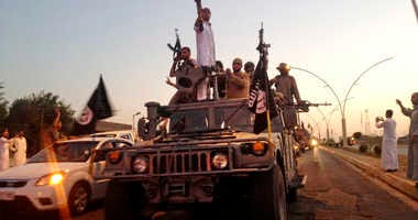 In this June 23, 2014 file photo, fighters from the Islamic State group parade in a commandeered Iraqi security forces armored vehicle on the main road in Mosul, Iraq.
