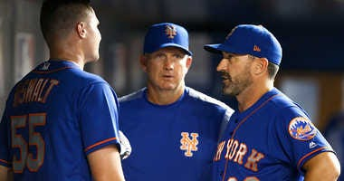 Dave Eiland (c.) and Mickey Callaway (r.) chat with pitcher Corey Oswalt in dugout.