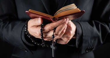 Priest holds bible, rosary beads