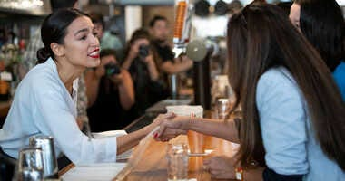 U.S. Rep. Alexandria Ocasio-Cortez (D-NY) shakes hands with people as she works behind the bar at the Queensboro Restaurant,