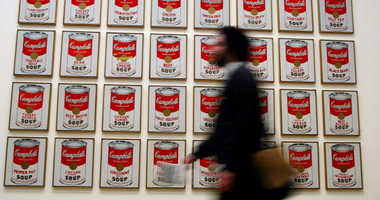 A spectator walks past 'Campbells Soup Cans' created in 1962 by artist Andy Warhol at the Andy Warhol retrospective exhibition