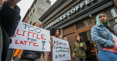 Protesters gather outside of a Starbucks in Philadelphia, Sunday, April 15, 2018, where two black men were arrested Thursday after employees called police to say the men were trespassing. The arrest prompted accusations of racism on social media.