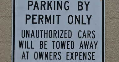 Parking By Permit Only Unauthorized Cars Will Be Towed Away At Owners Expense sign.